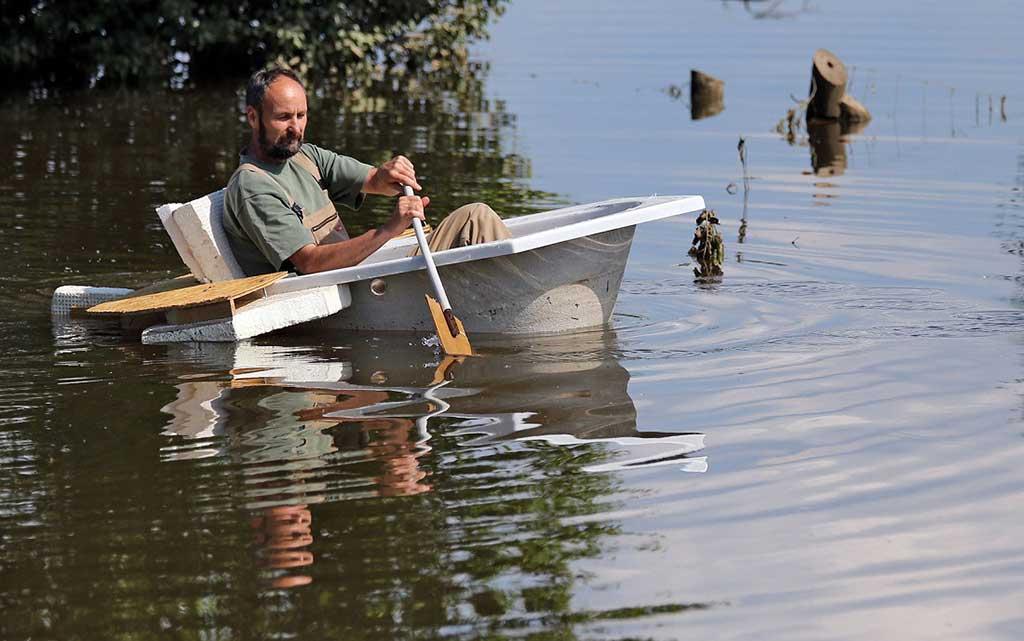 мужчина в ванне с веслами плывет по реке