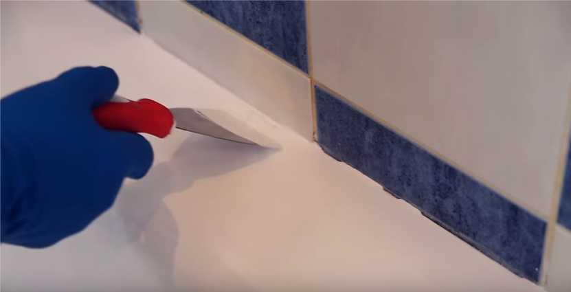 Корректируем покрытие шпателем в местах стыка ванны и кафеля