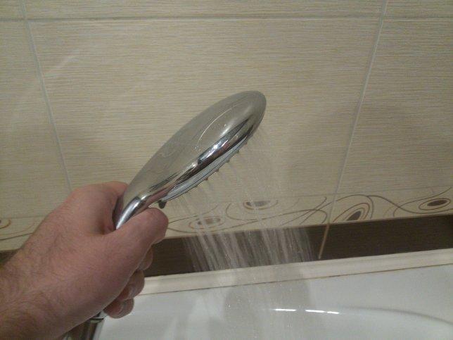 Рука держит душевую лейку с льющейся водой